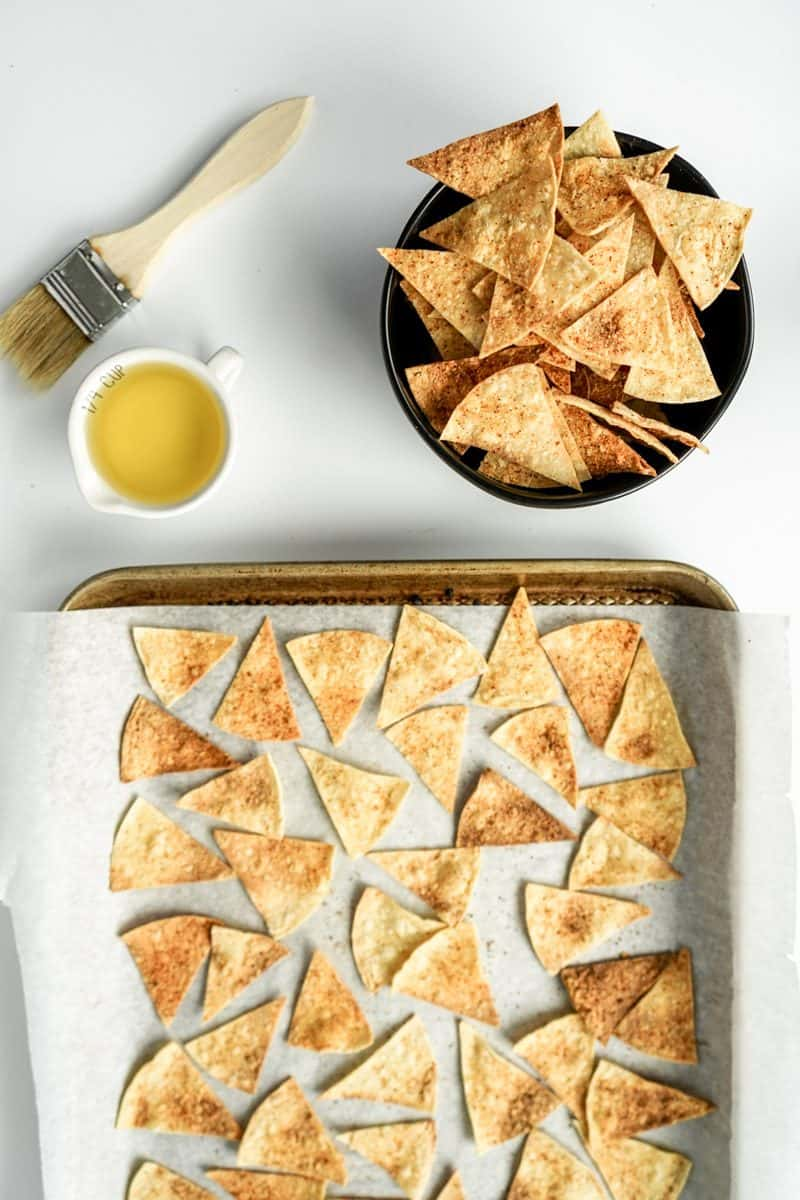 bowl of tortilla chips with a pan of baked chips on it.  paint brush with cup of olive oil next to the bowl and pan.