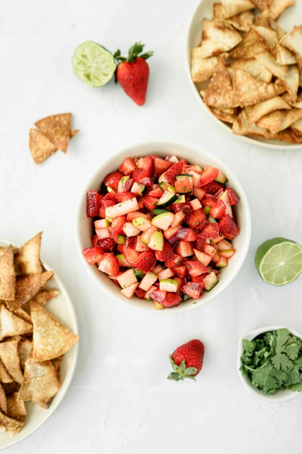 Bowl of fresh strawberry fruit salsa with two dishes of cinnamon sugar tortilla chips.