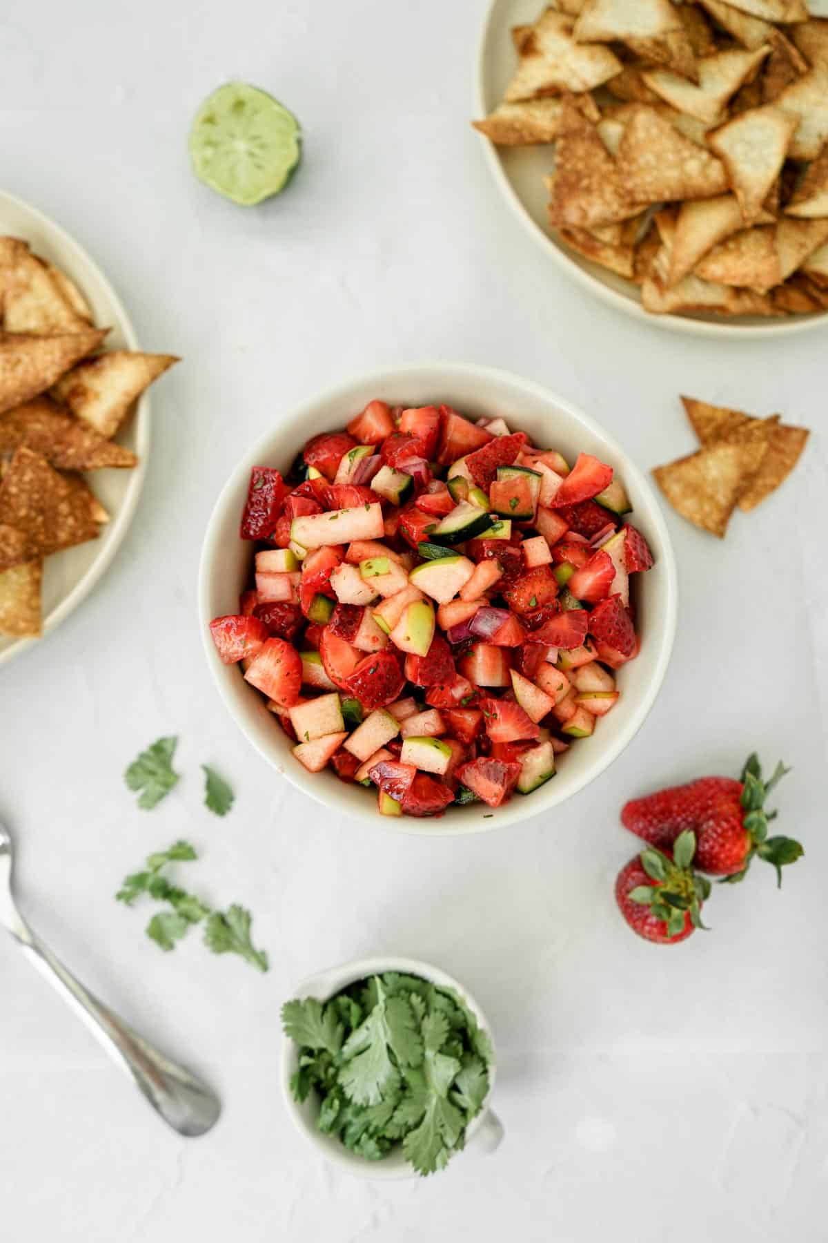 Bowl of fresh strawberry fruit salsa with homemade cinnamon sugar pita chips and other ingredients placed around the bowl