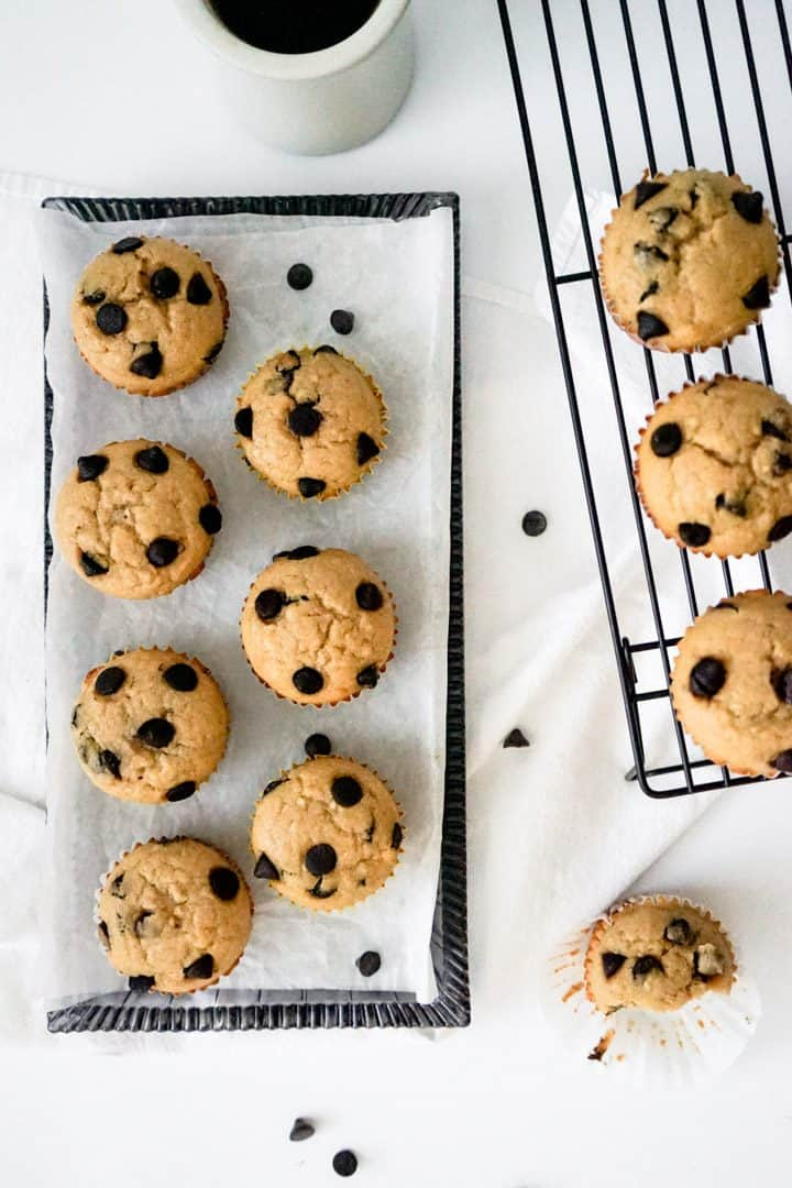 Plate of espresso chocolate chip muffins next to a cooling rack with more muffins.
