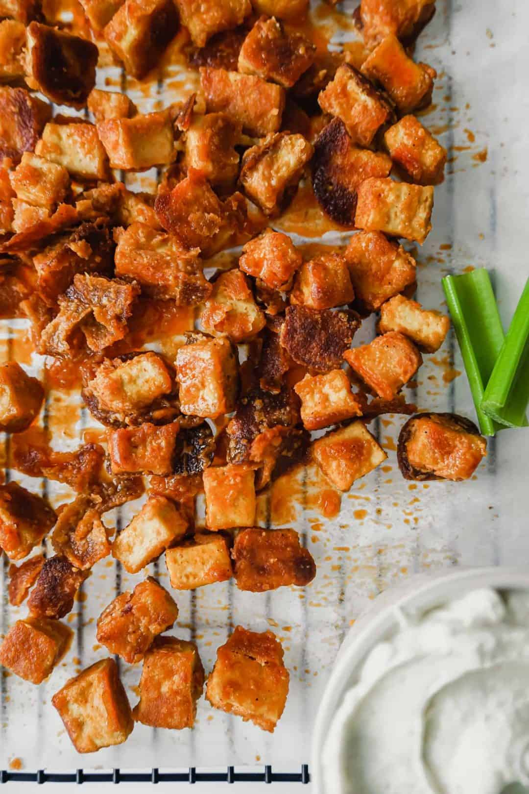 A tray of crispy buffalo tofu bites with a bowl of Greek yogurt Ranch dip in the bottom right corner and two celery sticks to the right.