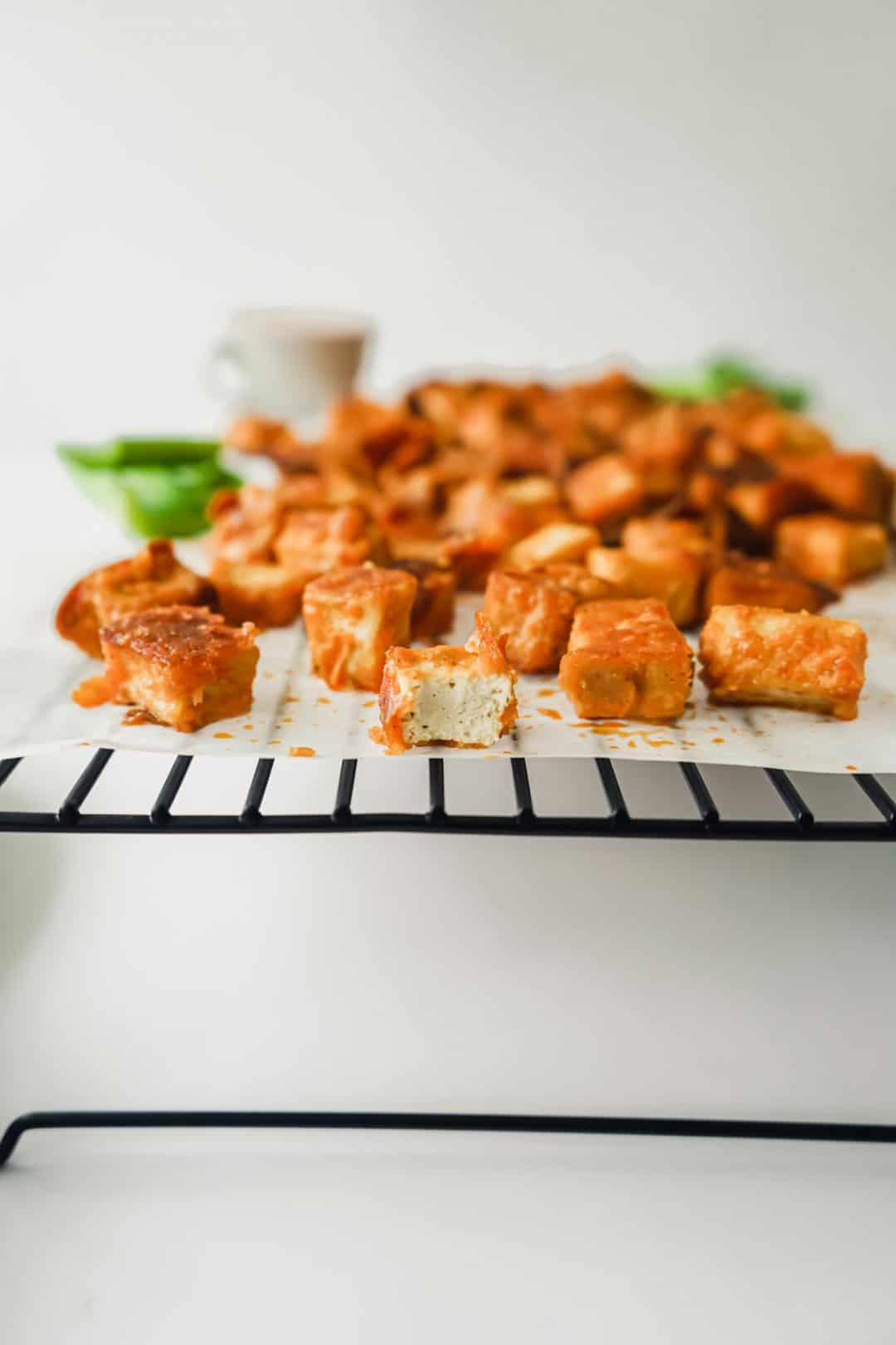 A tray of crispy buffalo tofu bites with a bite taken out of one.