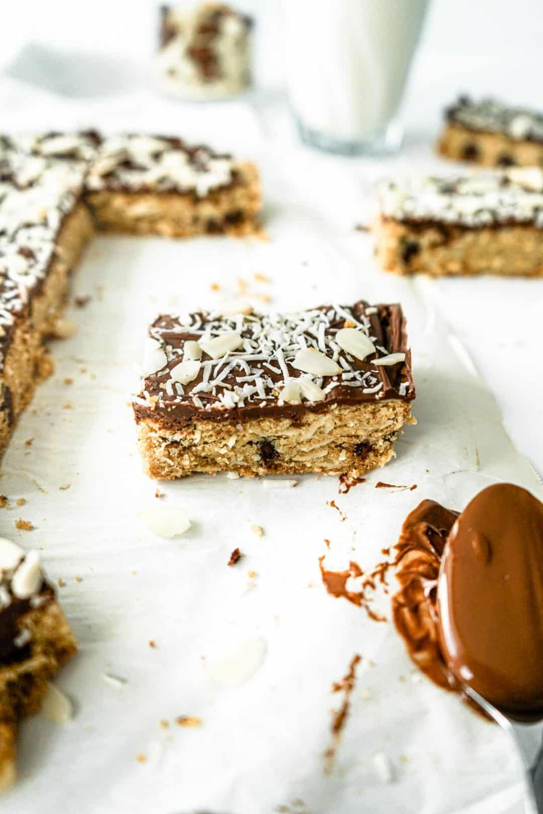 An almond joy cookie bar with a spoon of melted chocolate in the bottom right corner and more almond joy cookie bars scattered around.