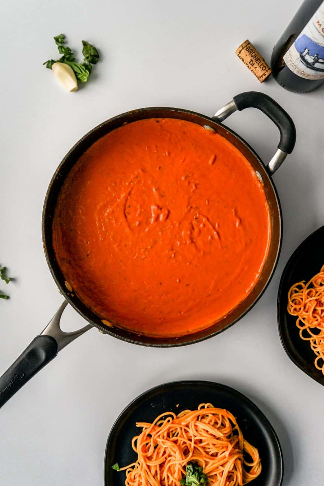 A large saucepan full of creamy tomato sauce with two plates of pasta, a garlic clove and basil leaves, and open bottle of wine around the pan.