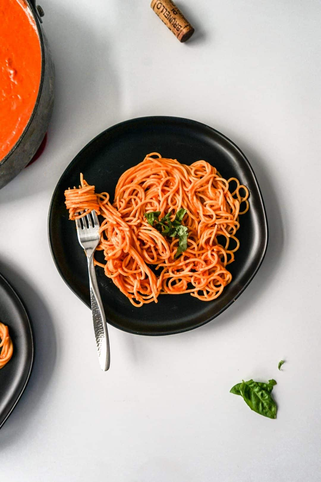 Plate of spaghetti with creamy tomato sauce and another plate and pan of more sauce to the left.  A wine cork and basil leaves are placed around the scene.